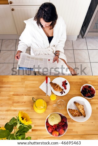 Young woman enjoying her lushious Sunday morning breakfast, reading a paper - stock photo