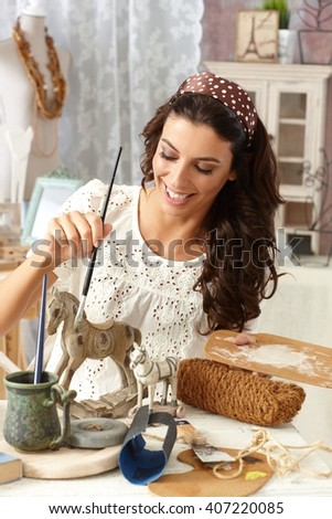 Young woman enjoying hobby painting in vintage style at old-fashioned home, smiling. - stock photo