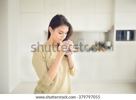 Young woman enjoying,holding cup of hot beverage,coffee or tea in morning sunlight.Enjoying her morning coffee in the kitchen.Savoring a cup of coffee breathing in the aroma in bliss and appreciation - stock photo