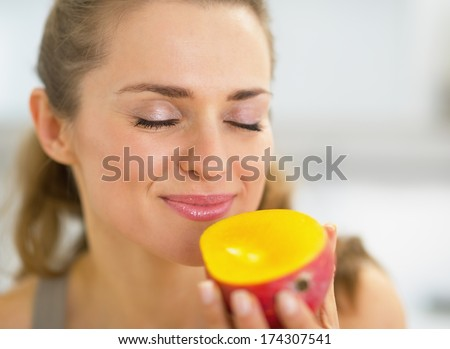 Young woman enjoying mango - stock photo