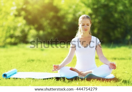 young woman enjoying meditation and yoga on green grass in the summer on nature - stock photo