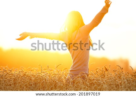 Young woman enjoying nature and sunlight in straw field - stock photo