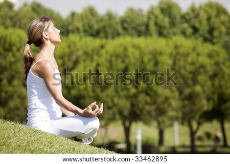 young woman enjoying nature in a yoga pose - stock photo