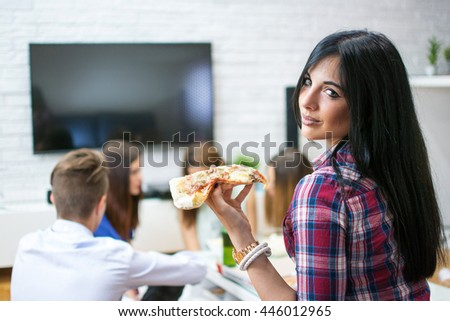 Young woman enjoying slice of pizza while sitting with her friends at home. - stock photo