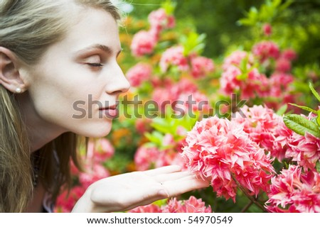 Young Woman Enjoying Smelling Pink Flowers - stock photo