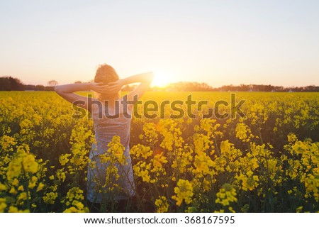 young woman enjoying summer and nature in yellow flower field at sunset, harmony and healthy lifestyle - stock photo