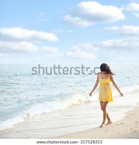 Young woman enjoying summer breeze at the beach. - stock photo