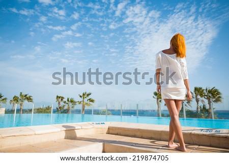 Young woman enjoying sun by pool at tourist resort - stock photo