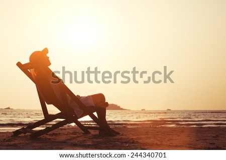young woman enjoying sunset on the tropical beach - stock photo
