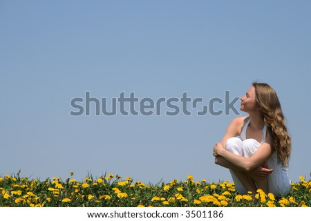 Young woman enjoying sunshine in a flowering spring field. - stock photo