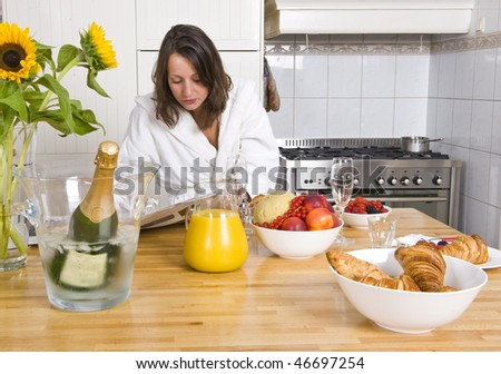Young woman enjoying the morning paper during a cozy champagne breakfast - stock photo