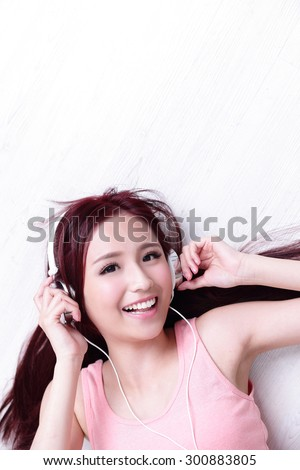 Young woman enjoying the music and relax lying at home, asian beauty - stock photo