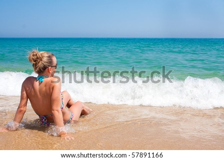 Young woman enjoying the ocean waves - stock photo