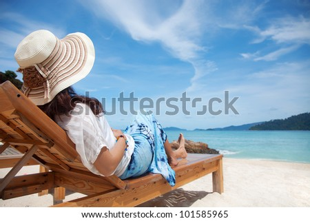 Young woman enjoying the sea view sitting on a beach's chair close to the sea - stock photo