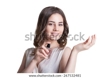 young woman enjoying the smell of the perfume on her wrist - stock photo