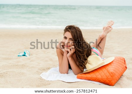 Young woman enjoying the sun sitting on a beach close to the sea - stock photo
