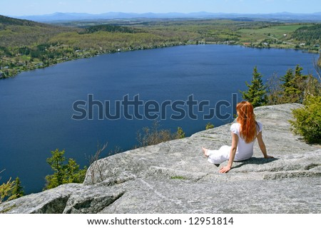 Young woman enjoying the view over lake from the mountain. - stock photo