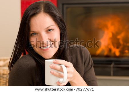 Young woman enjoying winter hot drink by home fireplace - stock photo