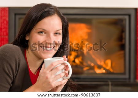 Young woman enjoying winter hot drink by home fireplace