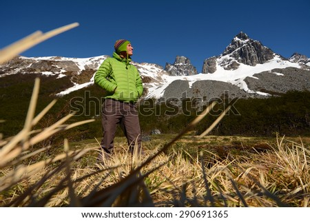Young woman enjoys beautiful view into high mountains, Patagonian Andes, South America - stock photo