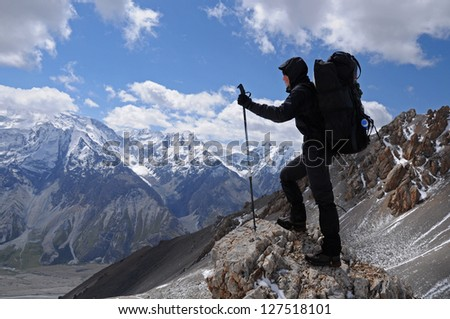Young woman enjoys spectacular view to high mountains