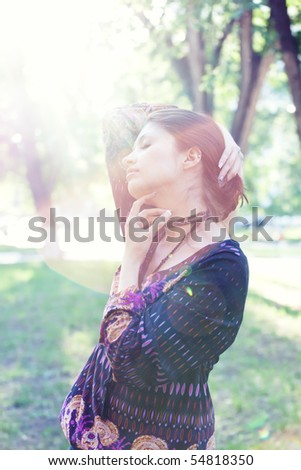 Young woman enjoys sun beams at spring park. Lens flares and low contrast. - stock photo