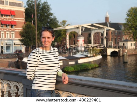 Young woman enjoys sunset light on the bridge in Amsterdam - stock photo