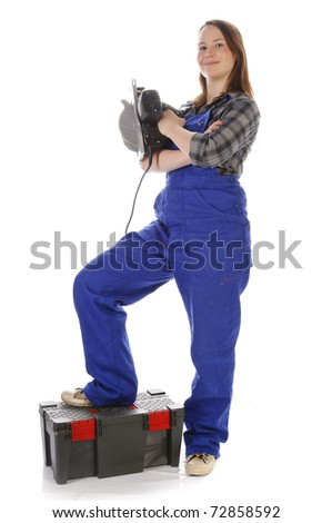 Young woman (Erin Crafts, DIY designer, trainee) with long hair wearing a plaid shirt and a blue work overalls. She is holding a electric skill saw in his hand. Isolated against a white background. - stock photo