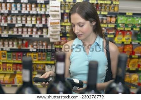 Young woman examining a bottle of wine with bottles in foreground - stock photo
