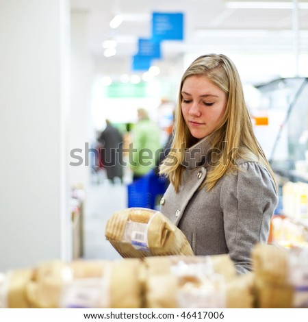 Young woman examining a loaf of bread at a supermarkets' bakery, with a shallow depth of field