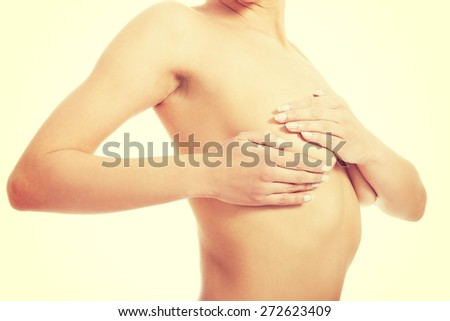 Young woman examining her breast - stock photo