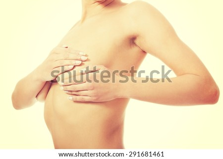 Young woman examining her breast