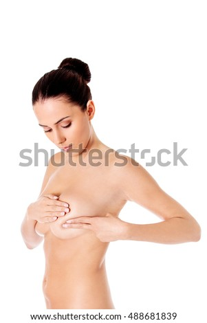 Young woman examining her breast for lumps or signs of breast cancer.