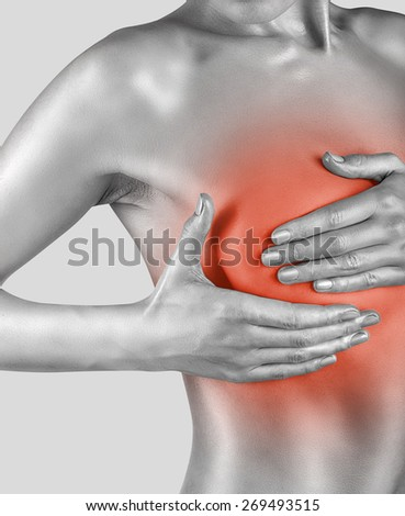 Young woman examining her breasts for signs of breast cancer isolated on white background - stock photo