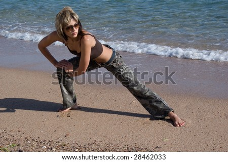Young woman excersising on the beach - stock photo