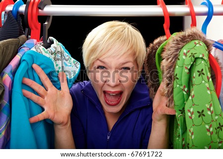 Young woman excited to choose her clothes - stock photo