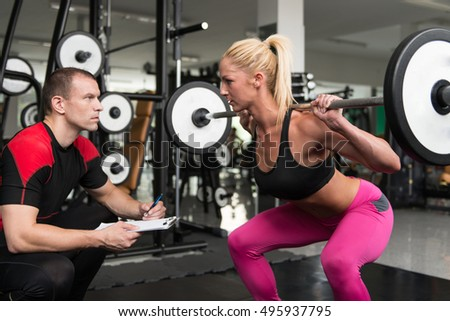 Young Woman Exercise Legs Squat  In The Gym While Personal Trainer Helps Out
