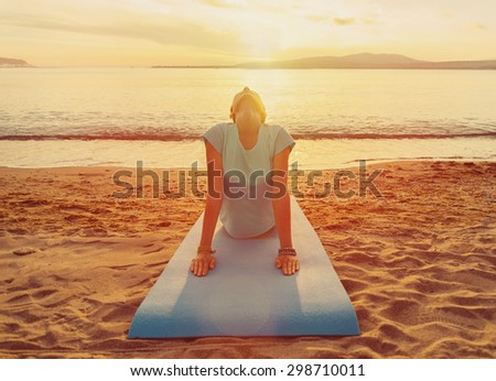 Young woman exercises on beach on background of sea at sunset in summer, woman stretching her back - stock photo