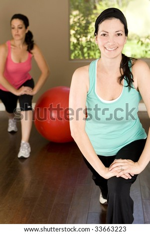 Young woman exercising at a gym - stock photo