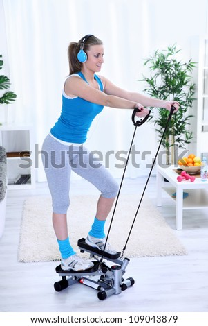 Young woman  exercising at home on stepper trainer - stock photo