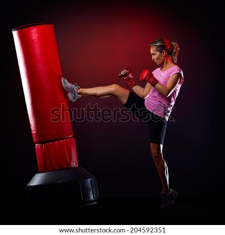 young woman exercising bag boxing in studio - stock photo