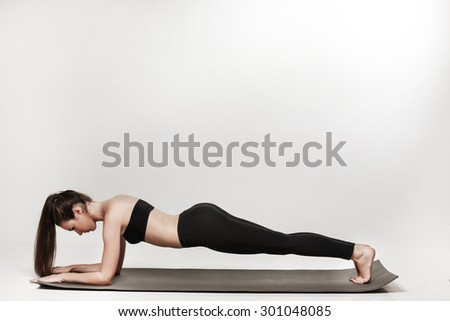 Young woman exercising. Fit sporty brunette doing a plank on yoga mat. Healthy lifestyle and sports concept. Series of exercise poses. Isolated on white. - stock photo