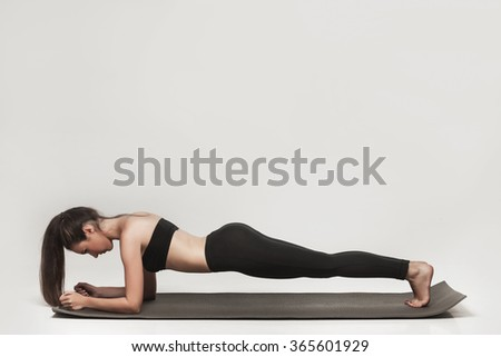 Young woman exercising. Fit sporty brunette doing a plank on yoga mat. Healthy lifestyle and sports concept. Series of exercise poses.  - stock photo