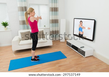 Young Woman Exercising In Front Of Television In Living Room - stock photo