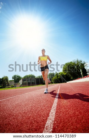 young woman exercising jogging and running on athletic track - stock photo