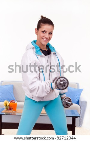 young woman exercising lifting weights at home