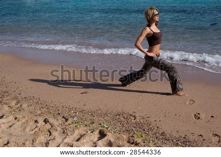 Young woman exercising next to sea - stock photo