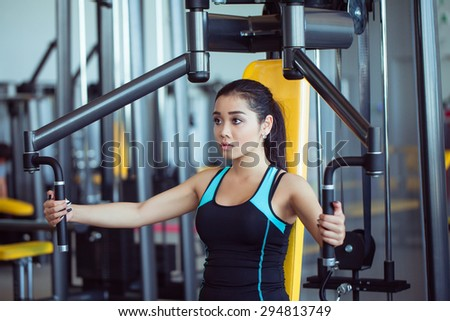 Young woman exercising on a machine in a gym - stock photo