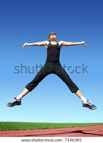 Young woman exercising on a racetrack - stock photo