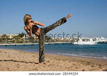 Young woman exercising on the beach - stock photo